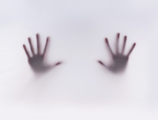 Hands of a young woman on a gray and foggy background
