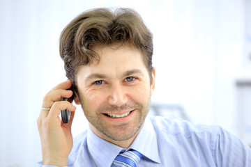 Handsome business guy working on cellphone and