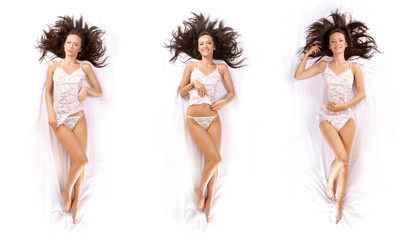 Three young brunettes in white lingerie are laying on silk