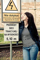 Attractive young woman licks danger sign