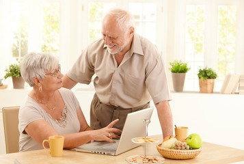 Happy senior couple with computer at home