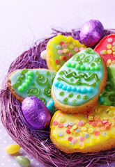 Colorful decorated easter cookies in nest