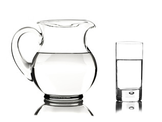 Glass and glass pitcher on white background