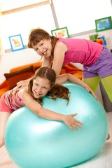 Little girls playing with exercise ball