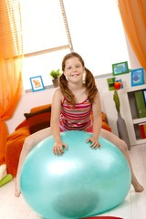 Young girl sitting on gym ball