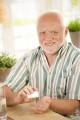Smiling senior taking medication