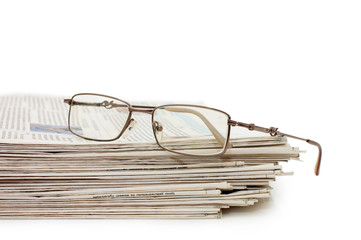 Eyeglasses on a pile of newspapers