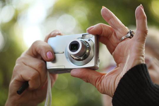 Senior woman hands holding compact photo camera