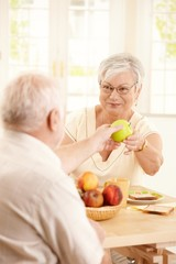 Smiling elderly wife handing apple to husband