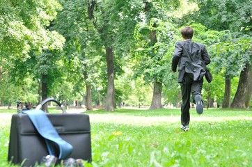 Business man running in park - escape