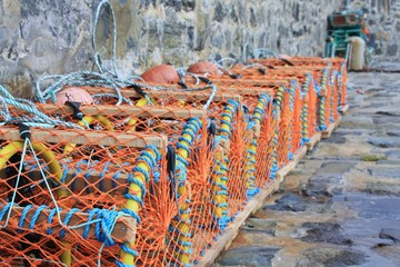 Row of lobster pots against harbour wall