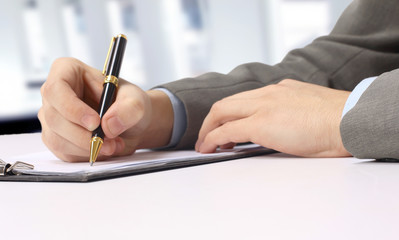 Close-up of business person hand with pen over