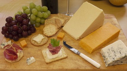Selection of cheese and crackers served on a wooden board