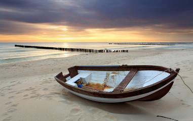 Obraz Łódź na pięknej plaży o wschodzie słońca - fototapety do salonu