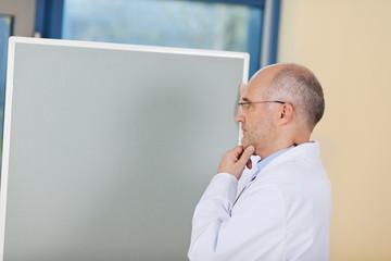 nachdenklicher arzt steht vor dem whiteboard