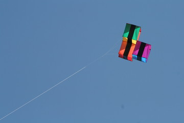 Multi Coloured Kite flying in bright blue sky