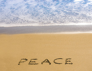 Peace written in the sand beside the sea