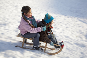 Children having fun on a sled in snow