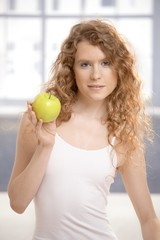 Pretty girl after workout with apple in hand
