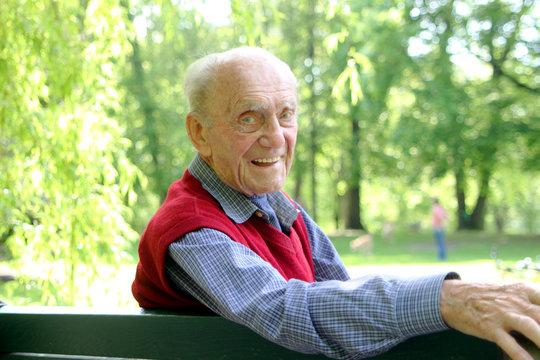 Alter Mann auf Bank im Grünen - lachend