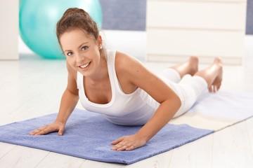 Pretty girl doing gymnastics on floor at home