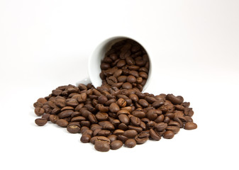 Overturned cup with coffee beans on white background