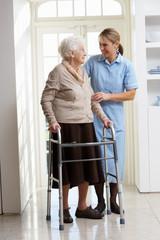 Carer Helping Elderly Senior Woman Using Walking Frame
