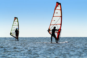 Silhouette of a two windsurfers