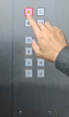 businessman hand press emergency  button in elevator