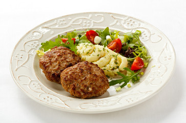 Fried steaks with mashed potatoes and vegetable salad