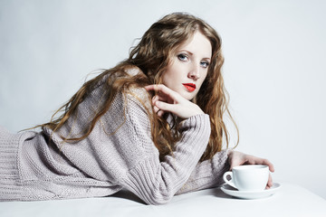 Portrait woman with a cup of coffee lying on a sofa