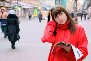 Beautiful young woman in the city street with magazine
