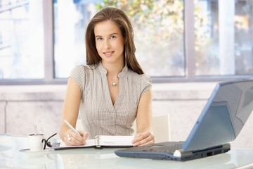 Smiling businesswoman at desk