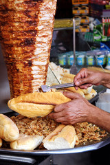 Hand filling up a full bread with kebab