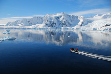 Wall Mural - boat cruises through antarctic landscape