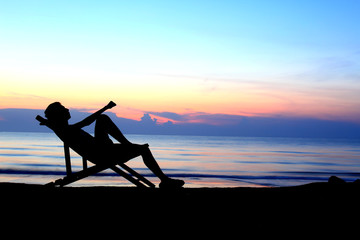 deckchairs and man on beach at sunset .