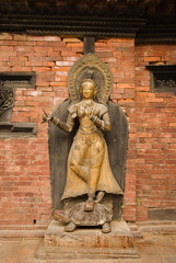 Bronze Deity at wall in Nepal temple 3.