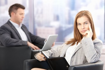 Attractive businesswoman sitting in office lobby