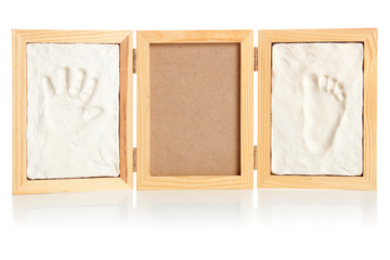 Blank photo frame with hand and foot prints of a child| Isolated