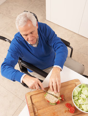 Disabled Senior Man Making Sandwich In Kitchen