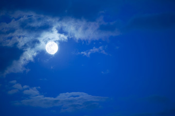 full moon over blue sky at a summer night with some clouds