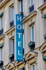 Enseigne Hôtel sur façade de pierre.
