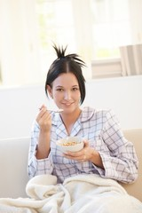 Portrait of woman having cereal on sofa