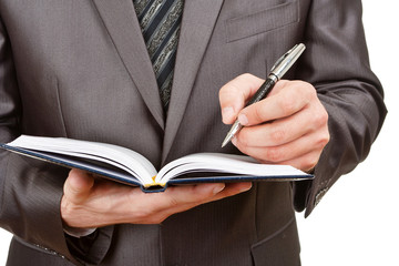 Fotobehang - Businessman writing in business diary