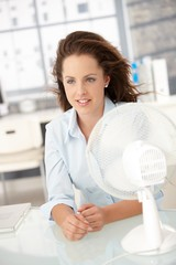 Young woman sitting front of fan cooling herself