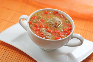 Home-made meatballs and vegetable soup, in a white soup cup
