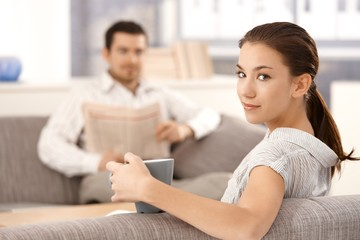 Young woman sitting on sofa man in background