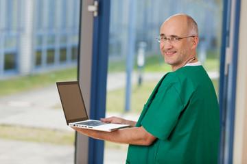 arzt im op-kittel mit laptop