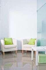 Brandable waiting room with two armchairs and white wall.