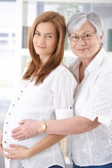Pregnant woman and mother smiling happily